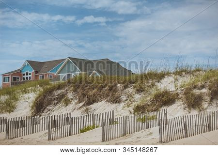 Big bright colorful ocean side beach house Outer Banks, North Carolina. Sand dunes, beach grass and wooden fence in the foreground, and clear blue sky with clouds in the background. stock photo