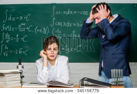 Man unhappy communicating. School principal talking about punishment. Teacher strict serious bearded man having conflict with student girl. Conflict situation. School conflict. Demanding lecturer stock photo