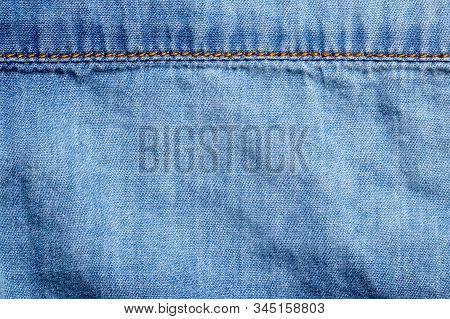 Denim background texture. Close-up of details of empty light blue jeans fabric jean surface with gold colored horizontal seam above. Macro. Top view. Beautiful backdrop with space. stock photo