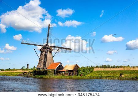 Famous windmills in Kinderdijk village in Holland. Colorful spring rural landscape in Netherlands, Europe. UNESCO World Heritage and famous tourist site. stock photo