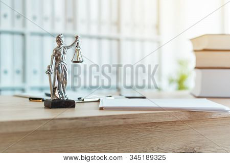 Lady Justice statue in law firm attorney office, blindfolded Justitia with balance scales and sword is personification of moral force in judicial system stock photo