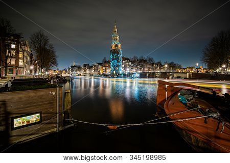 Amsterdam, Netherlands - December 29, 2019 : artfully lit tower with light project and passing boats at night stock photo