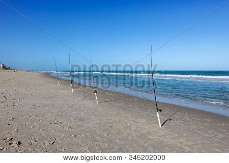 A row of fishing poles with lines cast into the Atlantic Ocean on a bright sunny blue sky day. stock photo