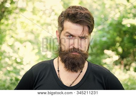 Beardy hipster. Brutal hipster on summer landscape. Bearded man in trendy hipster style outdoor. Caucasian hipster with thick beard hair and stylish haircut. stock photo