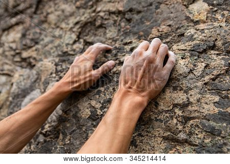 A closeup view of toned and muscular masculine arms scaling a sheer cliff. Man tries rock climbing. Adventure and success during recreational activity stock photo