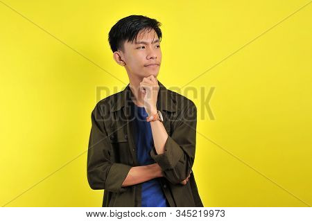 Handsome young Asian man looking at copy space or blank area, isolated on yellow background stock photo