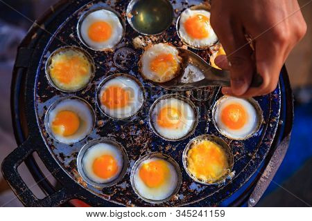 Traditional Thai Street Fast Food, quail eggs cooked in heating mantle (hot indented frying pan). Asian Cuisine, Delicacy, Culture, Cooking, Snack Food, Indulgence, Nutrition and Gourmet concept. stock photo
