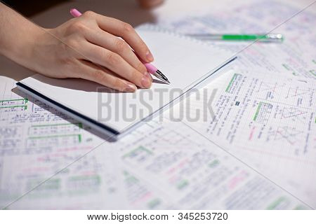 Hand Writes On A Blank Sheet In A Notebook Plans, Schedule, List, Completed Sheets Laid Out On A Tab