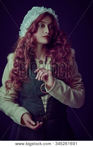 Portrait of a beautiful young woman with long red hair wearing medieval clothes on a dark green background. Historical reconstruction of the Middle Ages. stock photo