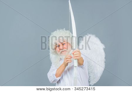Postcard for Valentines Day. Male angel Cupid with bow and arrows of love. Saint Valentines Day celebration. Valentines cupid with wings. Cupid firing arrow. Cupid Valentines day with bow and arrow. stock photo