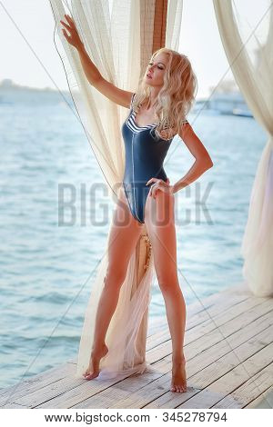 Adult woman 40-45 years old blonde with a perfect figure in a blue swimsuit. stock photo