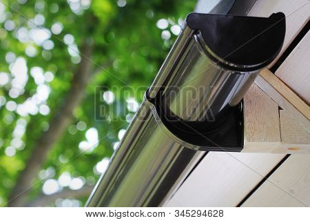 Rain Gutter Pipeline System Installation. Roofing Construction. Rain gutter system and roof protection from snow stock photo