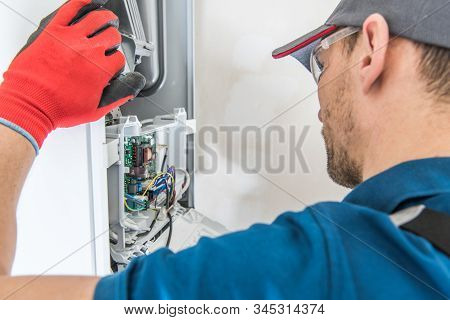 Technician Servicing Residential Heating Equipment. Central Heat Gas Furnace Issue. stock photo