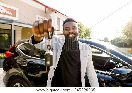 Portrait of African man car seller holding car keys. Attractive cheerful young African man smiling showing car keys to his new auto posing outdoors at the dealership salon stock photo