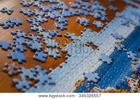 Partially solved jigsaw puzzle with scattered puzzle pieces on the table stock photo