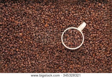 white cup with roasted beans on the coffee background. cup of coffee with grains on grain background. coffee beans top view. cup and beans view from above close-up brown texture backdrop stock photo