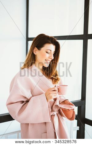 Beautiful girl in a bathrobe enjoying coffee at home. drinks morning coffee, good morning.Morning coffee is my daily routine.Cheerful young woman smiling and looking at the window stock photo