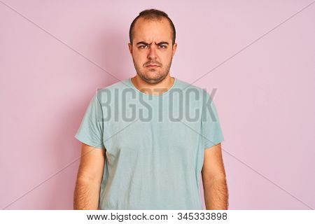 Young man wearing blue casual t-shirt standing over isolated pink background skeptic and nervous, frowning upset because of problem. Negative person. stock photo