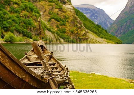 Old wooden viking boat on fjord shore. Mountains and Sognefjord. Tourism and traveling concept stock photo