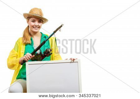 Fishery, spinning equipment, angling sport and activity concept. Happy woman with fishing rod holding blank white board with copyspace. stock photo