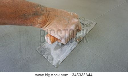 construction - plasterer concrete,loseup hand of worker plastering cement at wall for building house stock photo