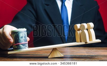 A man puts a bundle of dollars on the scales and outweighs the people. Taxpayers concept. Decent salary pay for staff specialists. Investments, deposits. Social project financing. Human trafficking stock photo