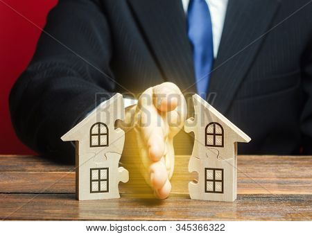Lawyer divides the house into two equal parts in a divorce process. Protection of rights. Conflict resolution. Court, justice. Disputes over fair division of marital property real estate. stock photo