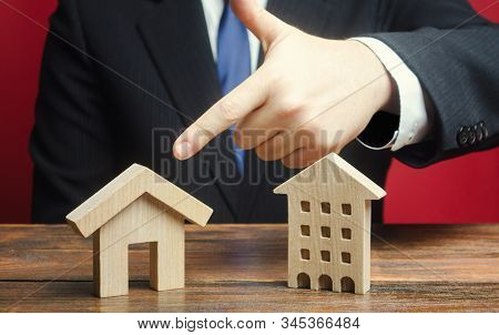 A man prefers to choose a private house rather than an apartment residential building. Definition for current needs, location. Choice of housing options. Type of optimal convenient housing. stock photo