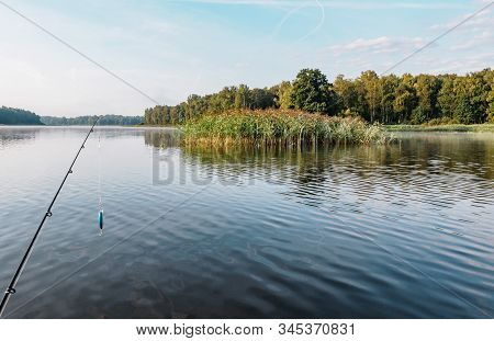 Fishing on the inflatable boat on the river. Inflatable kayak with rod with spoon n the summer day on the river. Leisure on water. Activities outdoor. Fishing from a boat. Handheld shot oning boat. Fishing rod and reel in shot. stock photo