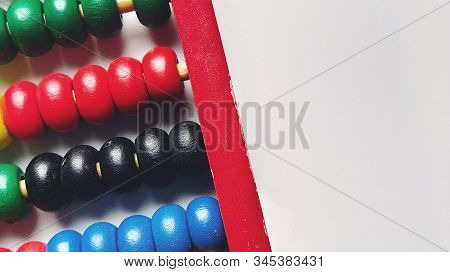 Wooden abacus. Red wooden frame with cross rods. Red, blue, yellow, green, black wooden elements. Math tool on a white background. Close-up. Copy space stock photo
