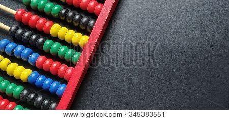 Wooden abacus. Red wooden frame with cross rods. Red, blue, yellow, green, black wooden elements. Math tool on a black background. Close-up. Copy space stock photo