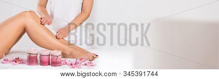 Beautician Waxing A Woman's Leg Applying Wax Strip stock photo