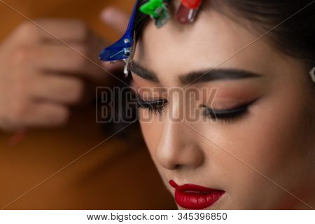Beautiful young asian bride. Attractive beautiful young asian woman making hairdo by hairstylist for wedding ceremony. Beauty girl get beautiful red lipstick, eyelash extensions, thick eyebrows stock photo