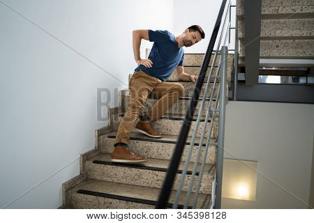 Man Lying On Staircase After Slip And Fall Accident stock photo