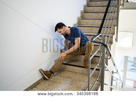 Man Sitting On Staircase After Slip And Fall Accident stock photo