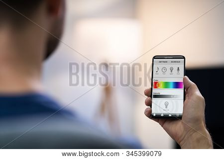 Close-up Of A Human Hand Adjusting Electric Light Through Mobile Phone At Home stock photo
