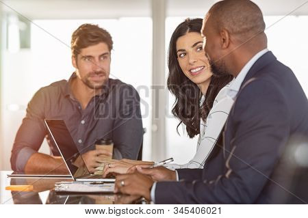 Multiethnic business partners discussing documents and ideas at meeting room. African businessman working with colleagues. Executive man planning work at meeting with businesswoman and associate. stock photo