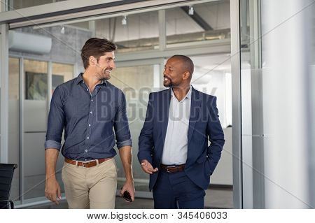 Multiethnic business colleagues walking in office while talking. Two successful business partners in modern office having conversation. Young businessman and mature boss discussing on new project. stock photo