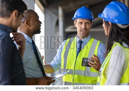 Happy mature engineer discussing the structure of the building with architects colleague at construction site. Engineers wearing safety hardhat having work conversation on the safety of the structure. stock photo
