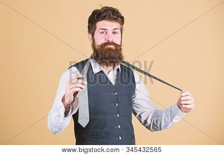 Art of manliness. Man bearded hipster try to make knot. Different ways of tying necktie knots. How to tie necktie. How to tie simple knot. Start with your collar up and the tie around your neck stock photo