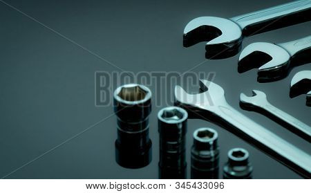 Set of chrome wrenches or spanners and hexagon socket on dark table in workshop. Chrome vanadium spanner wrench. Shiny silver wrenches and socket. Mechanic tools. Hardware for service technician. stock photo