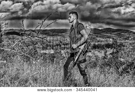 Regulation of hunting. Hunter rifle gun stand top of mountain. Guy bearded hunter spend leisure hunting on birds. Hunting hobby concept. Man muscular brutal guy gamekeeper nature background stock photo