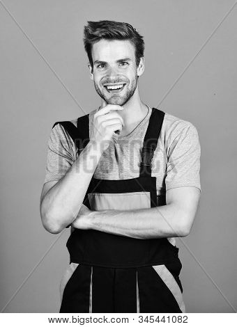 Confident mechanic. man build house. skilled architect repair and fix. building skills and construction. worker purple background. man builder in work clothes. professional repairman. turnkey project stock photo