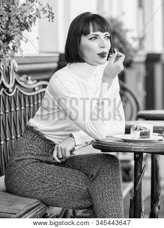 Pleasant time and relaxation. Delicious gourmet cake. Woman attractive brunette eat gourmet cake cafe terrace background. Gastronomical enjoyment. Gourmet concept. Girl relax cafe with cake dessert stock photo
