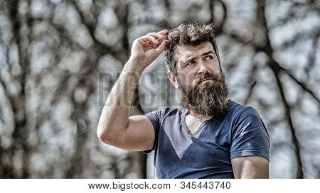 Confident posture of handsome man. Man attractive bearded hipster posing outdoors. Guy masculine appearance with long beard. Barber concept. Beard grooming. Beard care. Masculinity and manliness stock photo