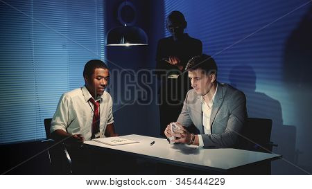 Accused young man crumpling a document with accusation in interrogation room after black detective gave him to sign it. stock photo