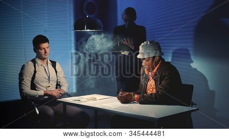 Suspected mixed-race man signing a document of accusation. Interrogation room in smoke. stock photo