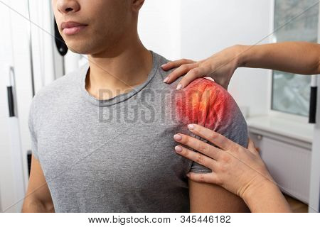 Athlete suffers from shoulder pain. Physiotherapist helps treat shoulder injury. Shoulder pain stock photo