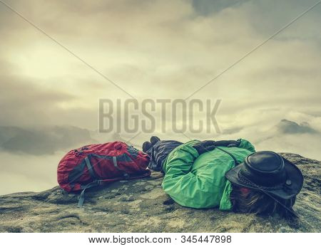 Hiker woman in hat lying on stone and relaxing in mountains. Alone hipster girl on top of mountain, resting, cowboy hat on her face stock photo