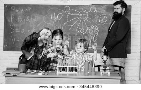 Topic of our club. Club include variety of activities with chemistry. School club education. Teacher and pupils test tubes in classroom. Chemistry themed club. Group interaction and communication stock photo